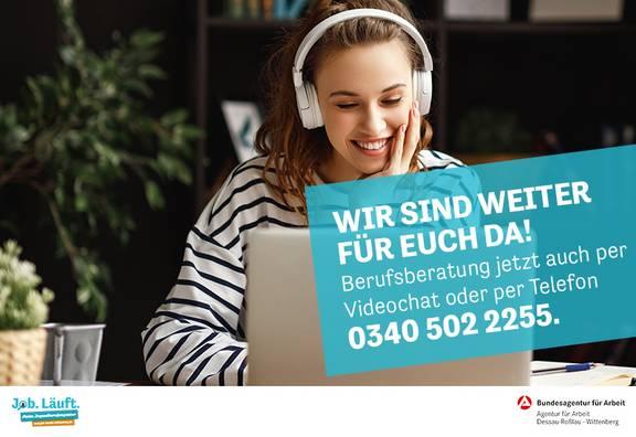 Mädchen sitzt am Laptop mit Kopfhörern