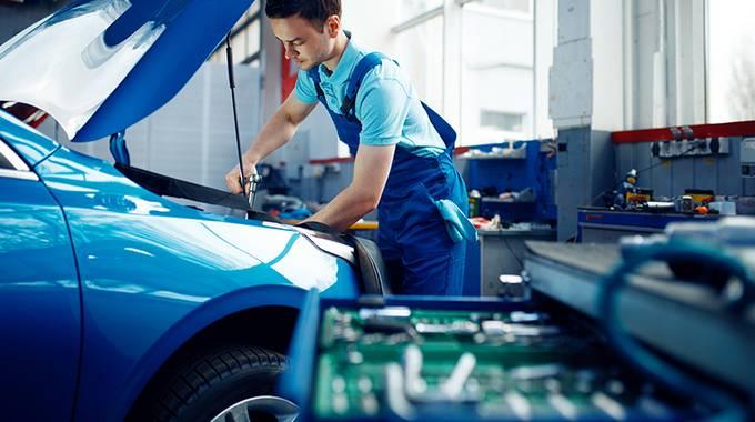 Auszubildender repariert ein Fahrzeug in der Werkstatt