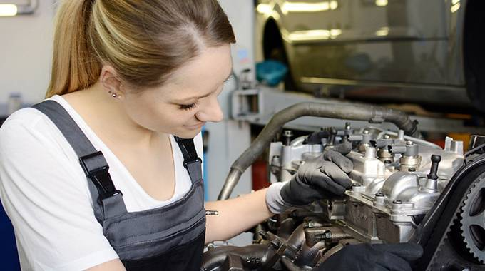 Mädchen repariert einen Automotor