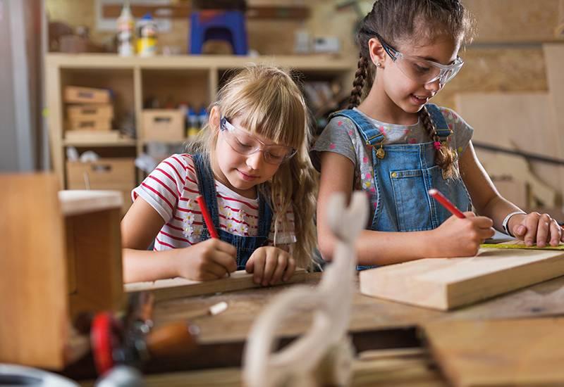Mädchen zeichnen auf Holz in der Werkstatt.